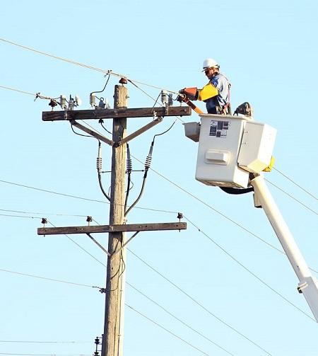 Professionnel travaillant sur le réseau électrique dans une nacelle