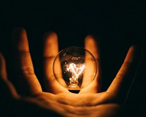 Ampoule allumée dans une main