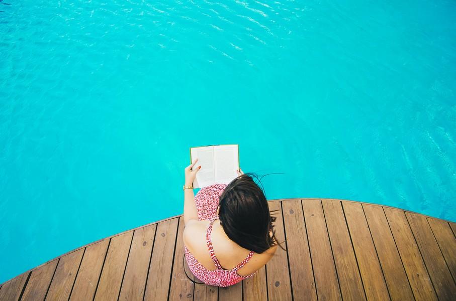 femme qui lit près d'une piscine en bois