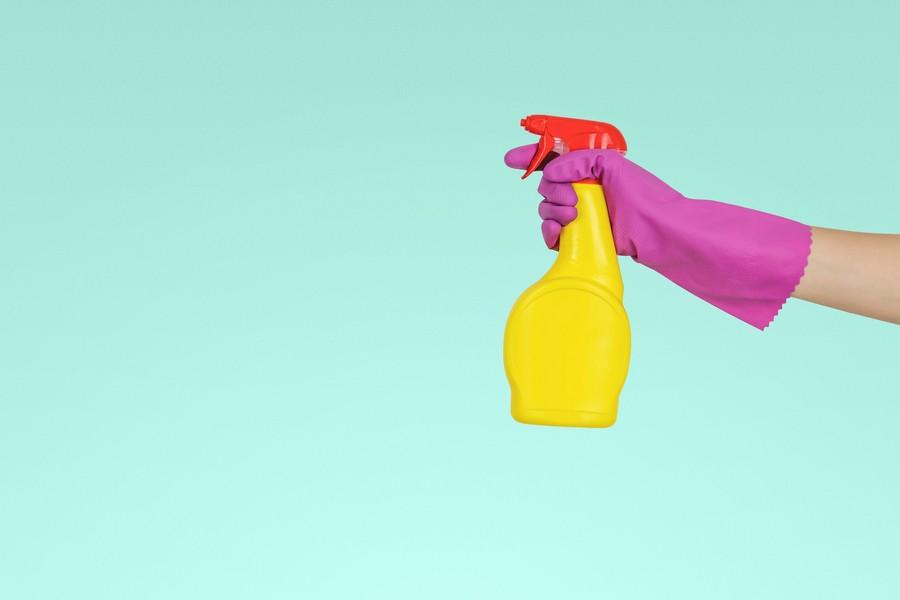 main avec un gant et un produit vaporisateur
