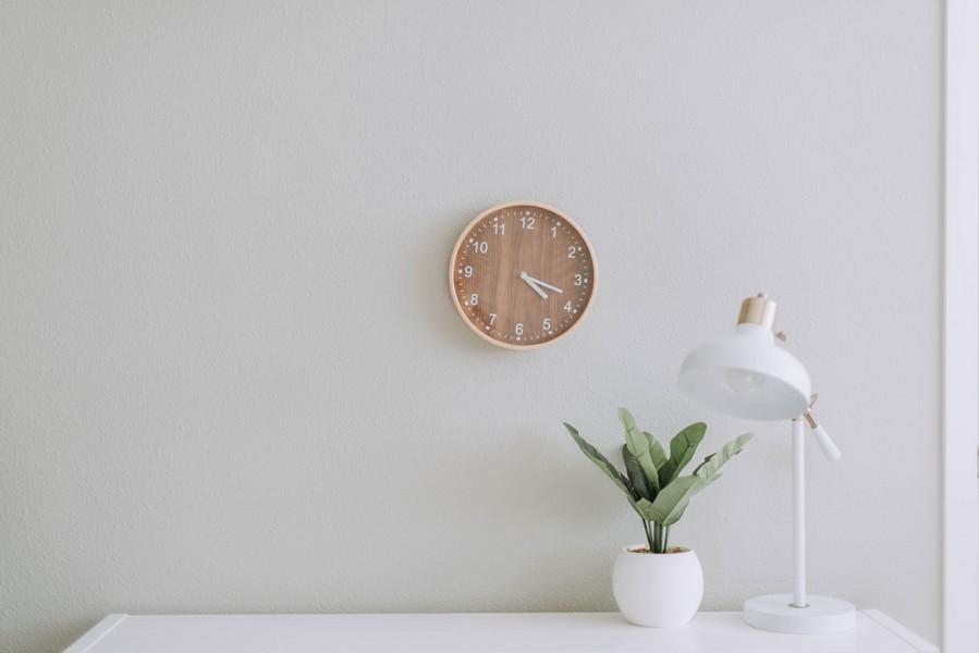 décoration de bureau minimaliste avec une horloge, une lampe et une plante