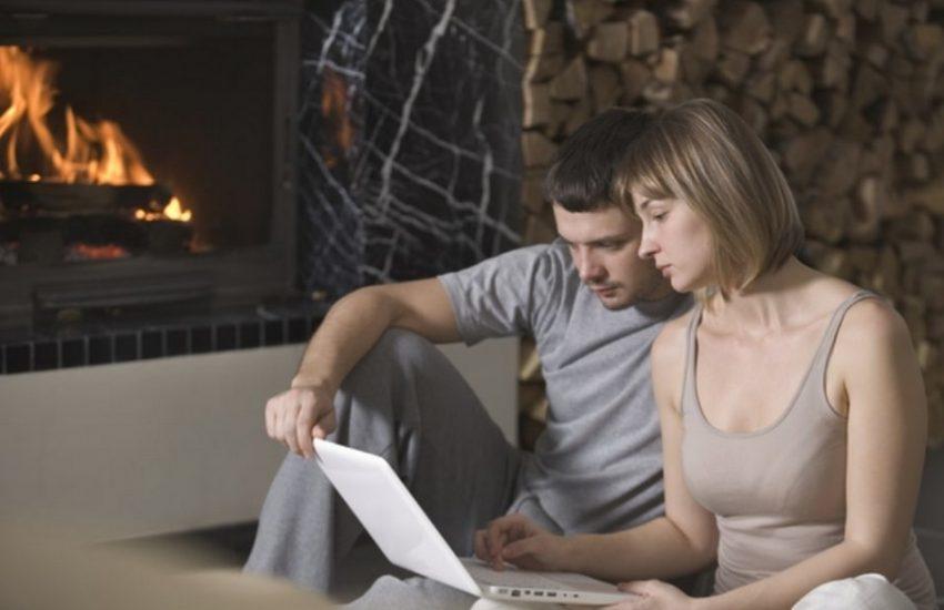 couple sur leur ordinateur près du feu dans le salon