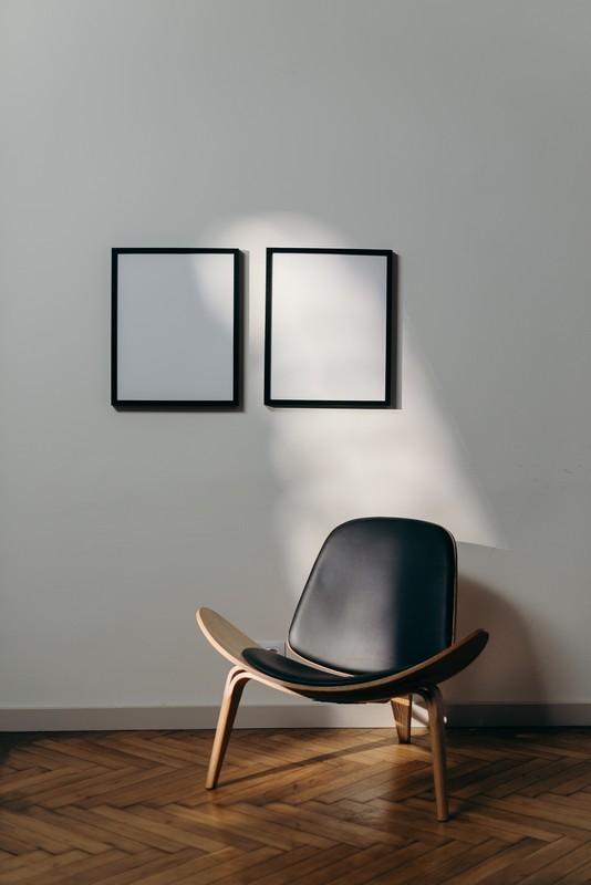 deux cadres sur un mur blanc avec une chaise devant